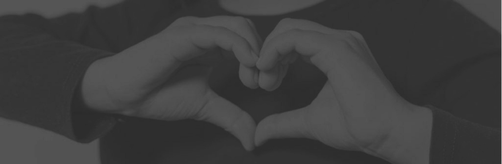 Photo of two hands creating the shape of a heart